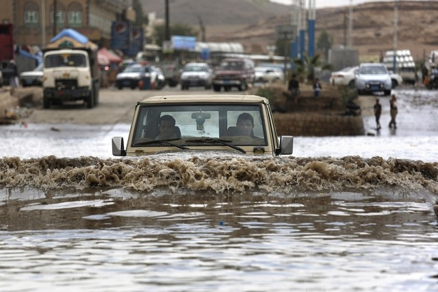 A motorist drives in floodwaters after a heavy rain in Sanaa, Yemen on April 13, 2016. Hani Mohammed/ AP Photo